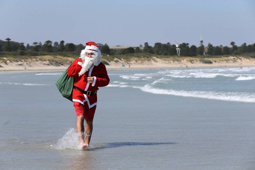 Santa walking along a beach delivering sunsmart tops