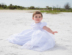 Baby in white dress at the beach.