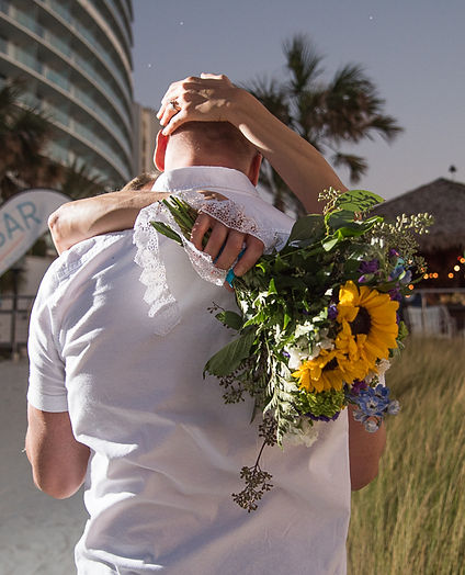 Bride kissing groom with bouqut of sunflowers in her hand at the Opal Sands Resort Clearwater, FL.