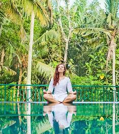 Woman meditation at gorgeous pool side of luxury tropical villa_edited.jpg