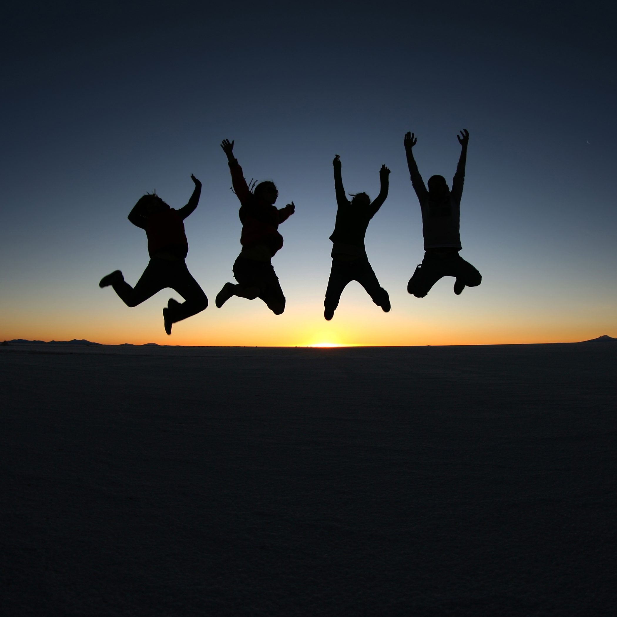 A group of happy young friends jumping i