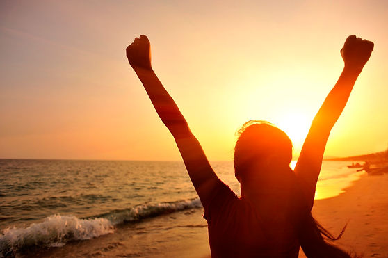 Woman-triumphant-on-beach-at-sunset.jpg