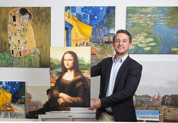 Gründer Benjamin Wild vor Gemäldeauswahl im Büro