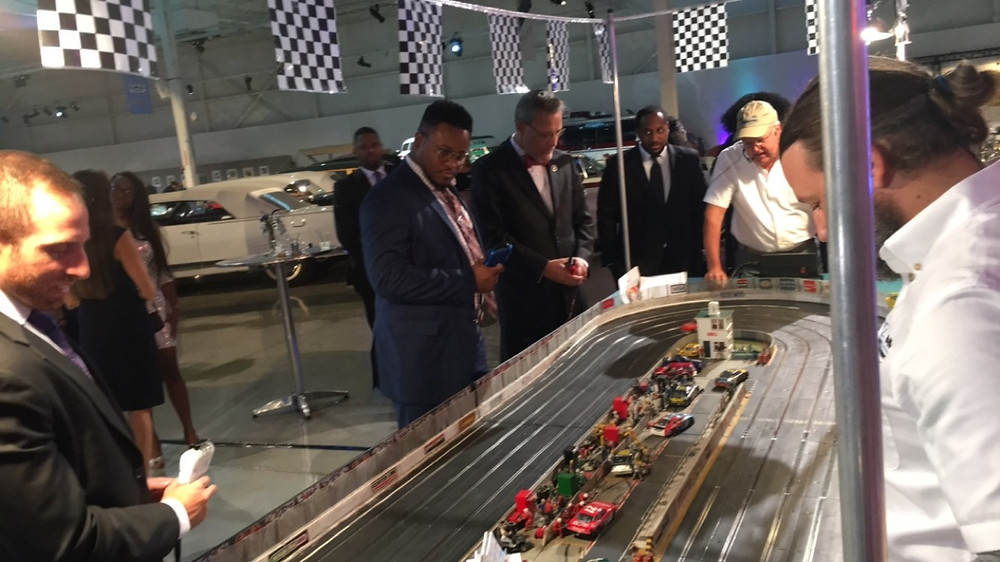 Alan Coleman (Strategic Staffing Solutions), and representatives from AAA Michigan, General Motors and Ally compete in the Sponsor Slot Car Race Competition.