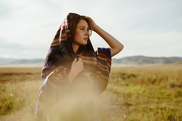 Girl looking into the distance corrects cape on her head standing on the grass in the step