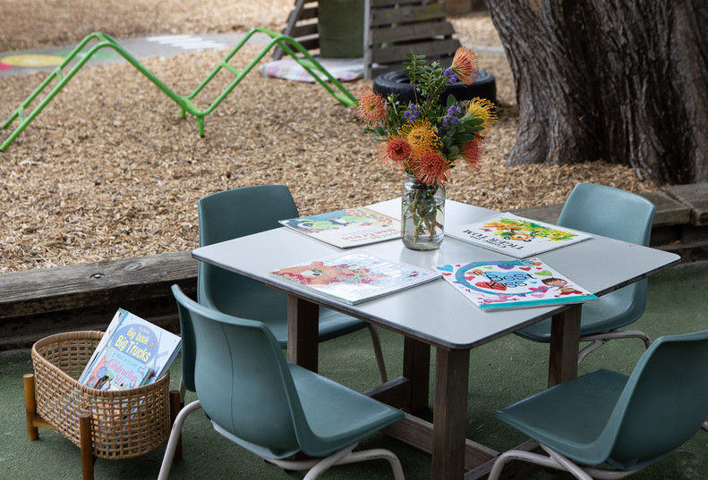 Reading book table ouside at Doncaster East Daycare & Kindergarten servicing the areas of Blackburn, Mitcham and Templestowe.