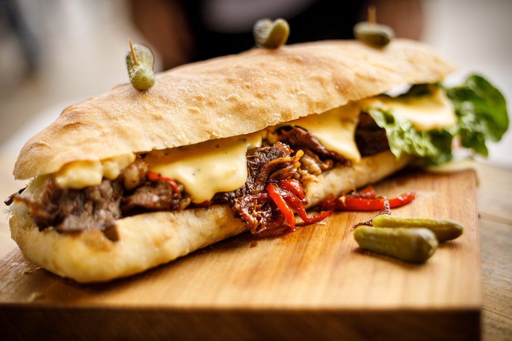Philly Cheesesteak is a classic American sandwich, comes with a combination of thinly sliced fried beef, peppers and onions in a big sandwich, deliciously oozing with loads of melted cheese. This is DAMN, the best Philly Cheesesteak ever.