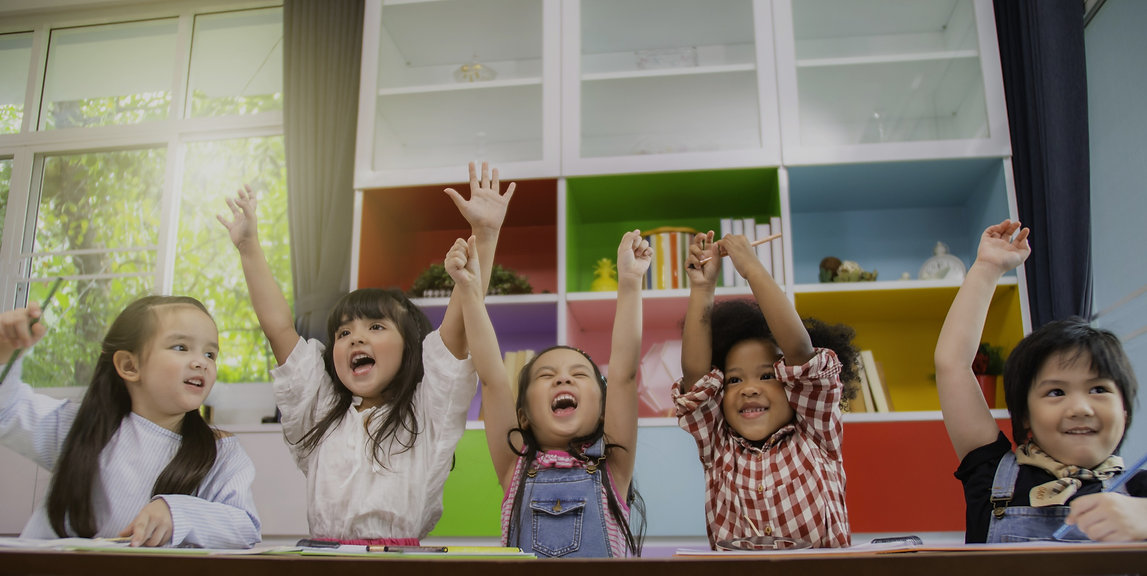 Excited children with their hands in the air