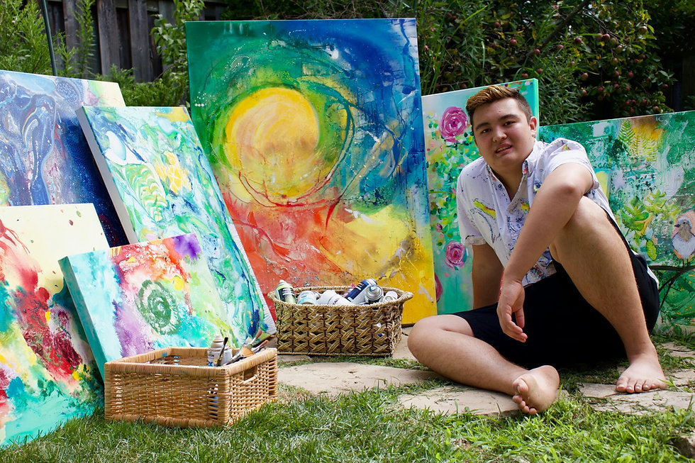Artist Aiden Lee sitting on the ground and surrounded by paintings.