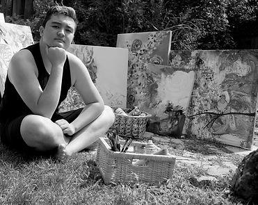 Artist Aiden Lee sitting on the ground outside surrounded by paintings and artist tools