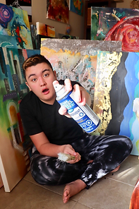 Artist Aiden Lee holding a spray paint can to the camera