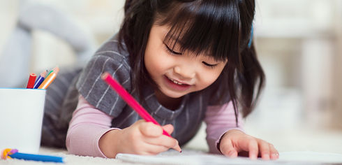 Smiling preschool child colouring a page