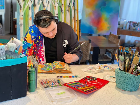 Artist Aiden Lee painting in a journal