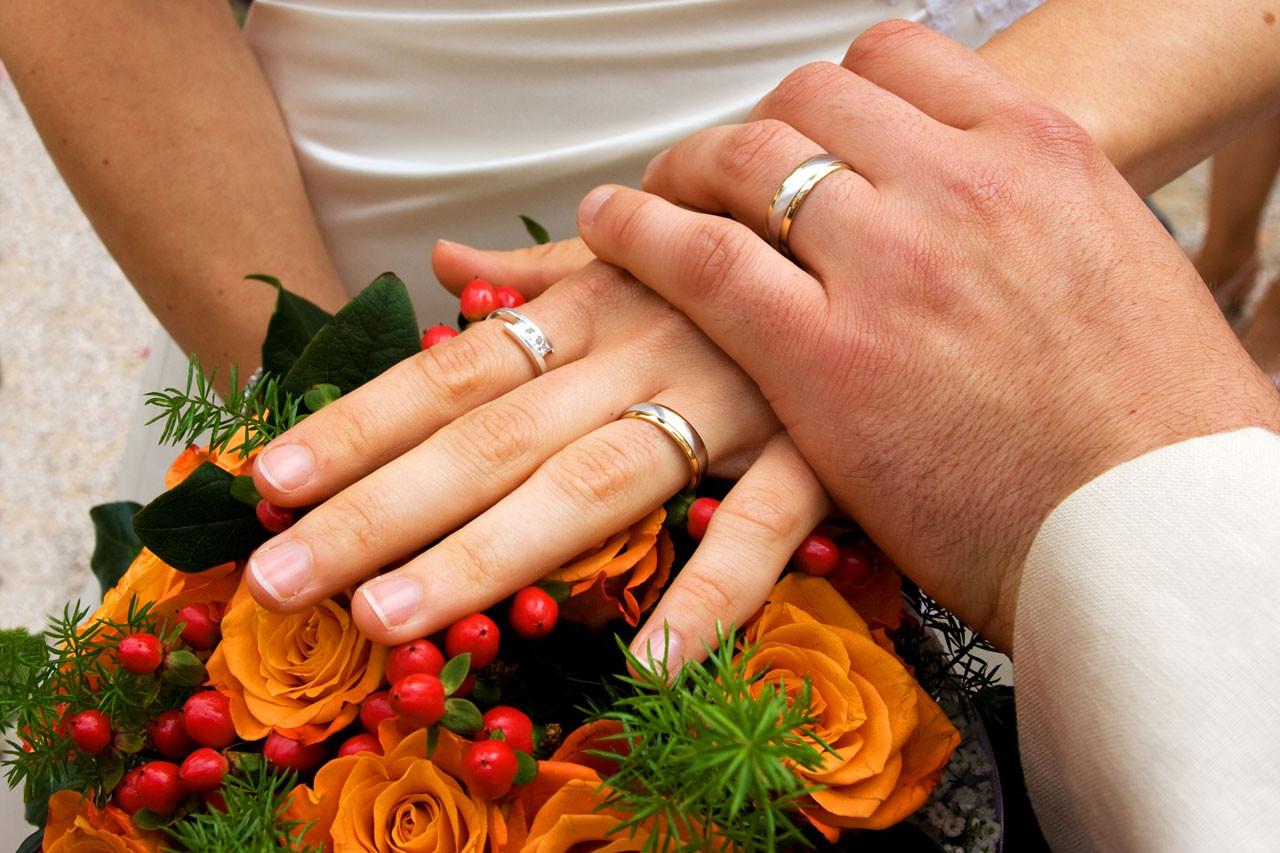 Haende mit Ringen auf Rosen