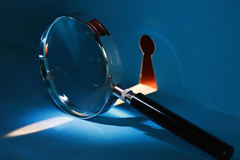 Spying concept. Magnifying glass near ke