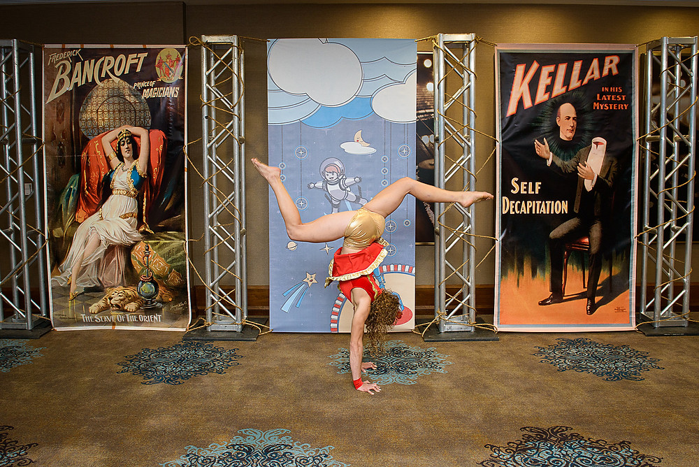 acrobat posing in front of vintage circus posters
