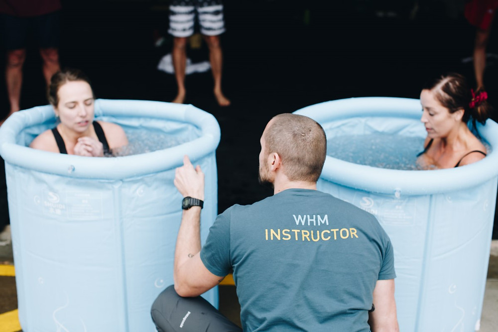 wim hof method workshop instructor with two women in ice bath