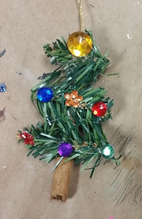 A piece of faux pine coiled to look like a mini Christmas tree. An assortment of beads and plastic gems are glued on top, and the base of the tree is a cinnamon stick.