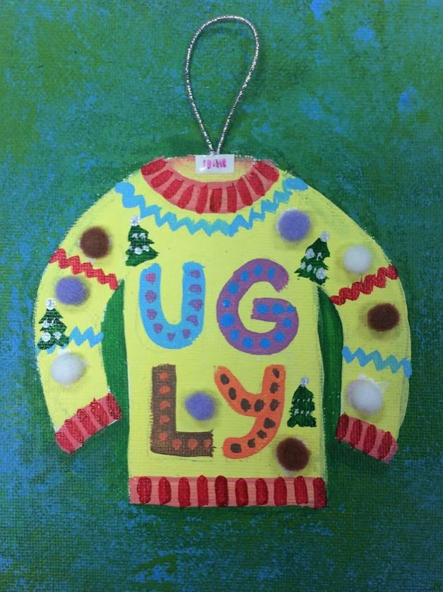 A bright yellow and red ugly Christmas sweater is painted onto a green background. A small piece of elastic string is glued to the neck hole to appear like an ornament.