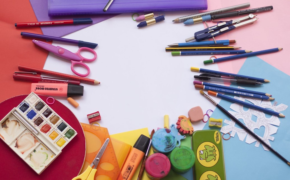 A multitude of art supplies organized in a rainbow.