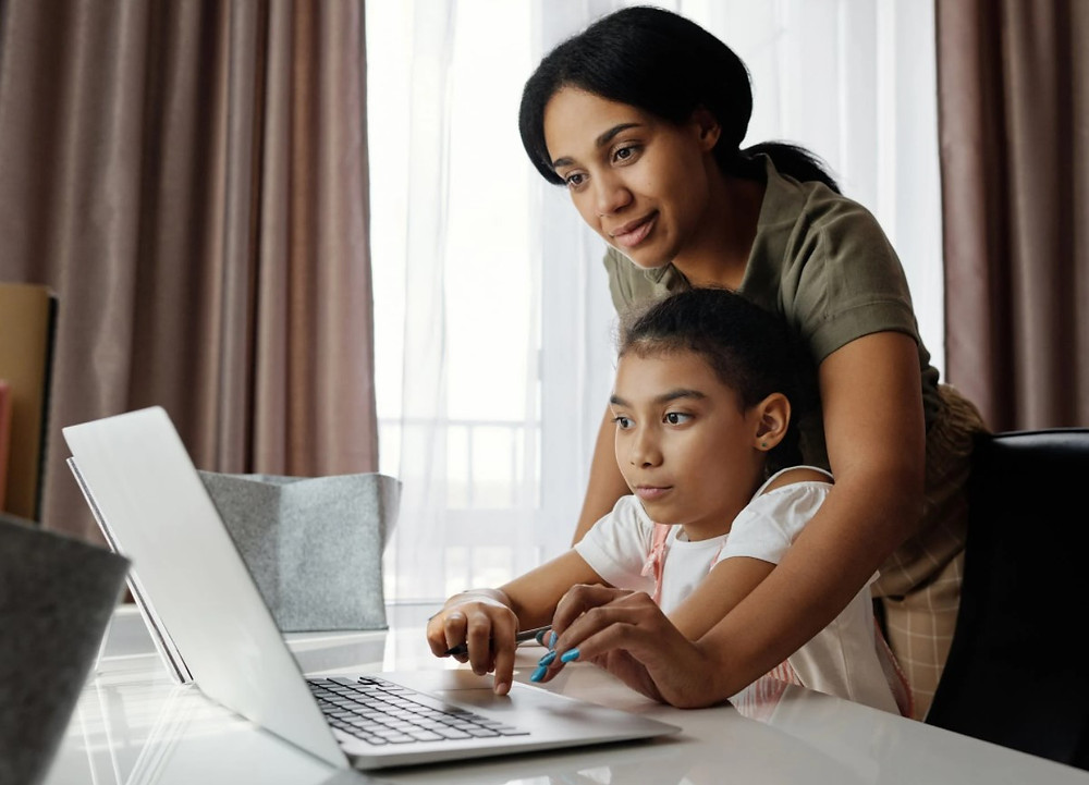A mother helping her child with a laptop.