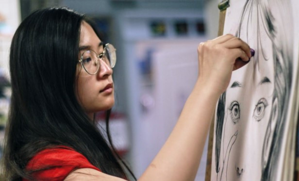 Instructor Rachael Ng illustrating a face on a piece of newsprint.