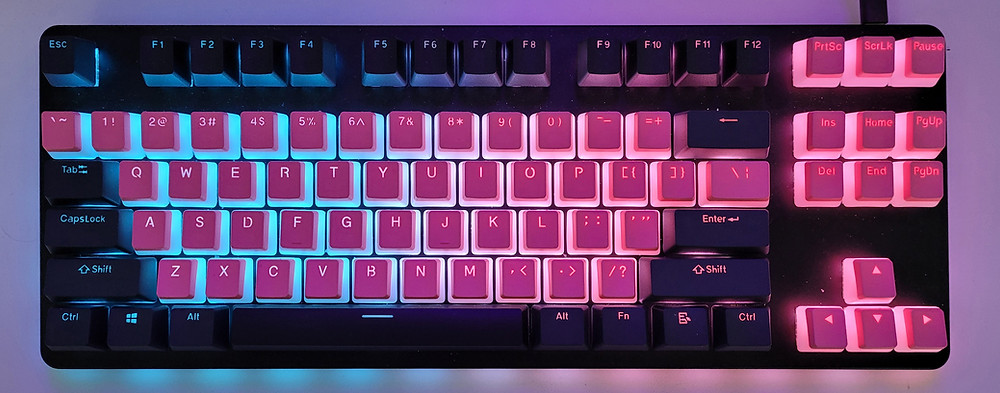 An image of a keyboard glowing pink and blue.