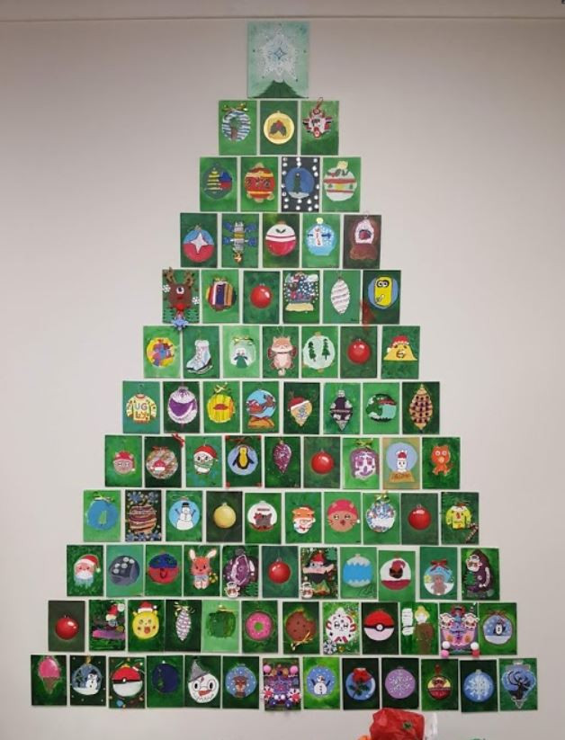 A Christmas tree made up of small rectangles of green paper. Each piece of paper has an illustrated ornament in the middle.