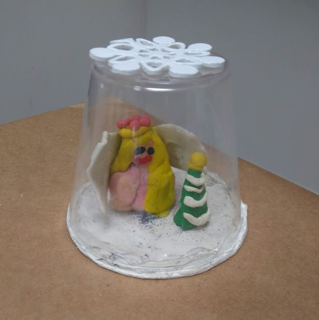 A mini diorama of an angel and a pine tree covered in snow. The diorama is sculpted in plasticine, and a clear plastic cup is glued on top.