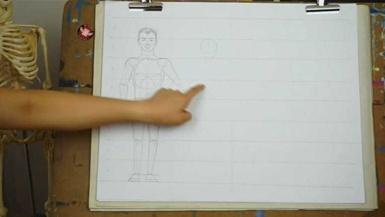 Fei Lu gesturing to her sketchpad. A finished male figure and the beginnings of the female figure have been drawn