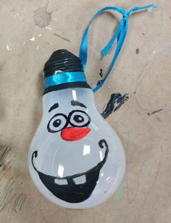 A lightbulb painted to have Olaf's face from Disney's Frozen on the front. A piece of blue ribbon is tied around the top.