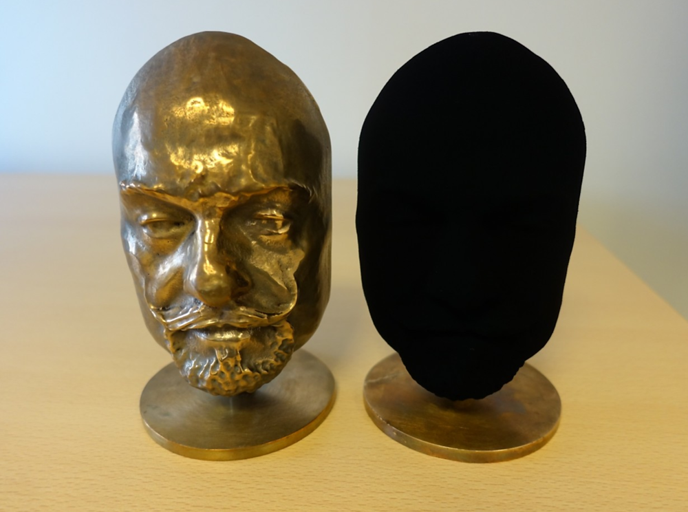 two heads made of brass, one is left untouched while the other is painted in vantablack