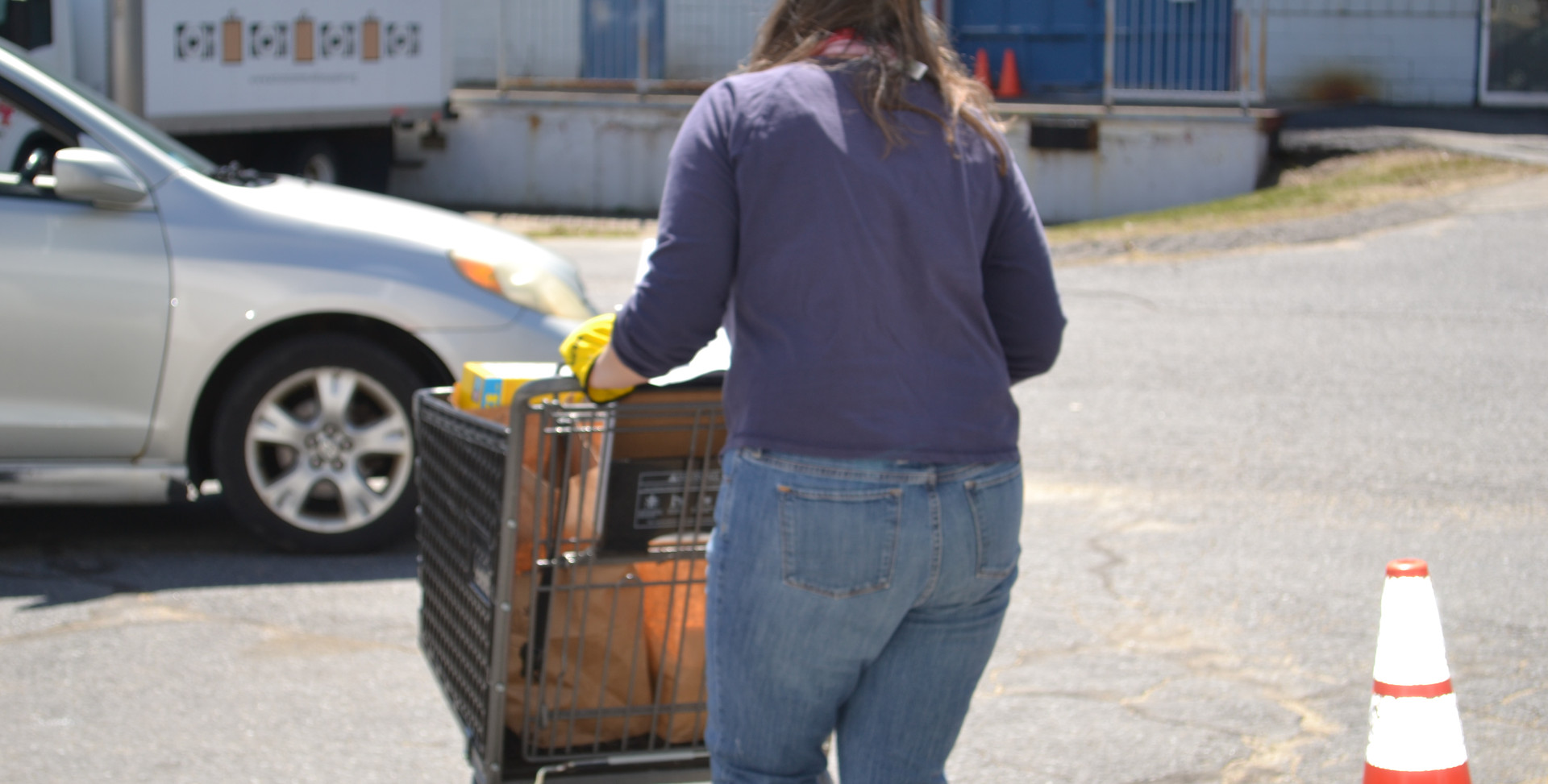 A volunteer brings food to a client's car