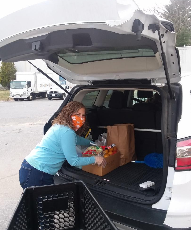Our volunteers load groceries into a client's car.