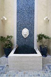 輸入住宅 外構施工実例。ライオンの吐水口とモザイクタイルの壁面が美しい壁泉。