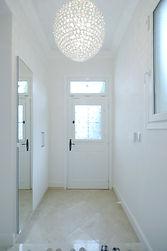 住宅施工例。玄関の上り口の段差をなくし、石の框は2色の大理石モザイクでデザイン貼り。