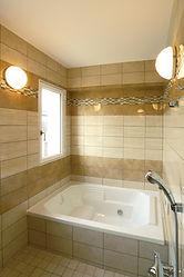 輸入住宅/住宅施工事例/光沢のある大理石調のタイルとボーダーアクセントのモザイクタイルが上質な空間の浴室。 