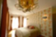 輸入住宅/住宅施工事例/盆栽の柄の壁紙が印象的な主寝室。照明はゴールドとガラスを用いた球状のペンダント。