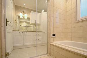 輸入住宅/住宅施工事例/タイルで仕上げたオーダーメイドのバスルーム。ガラス製の扉で空間を広く見せてくれる。