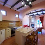 住宅施工例。見せ梁と色漆喰の壁のキッチン。