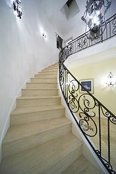 輸入住宅/住宅施工事例/緩やかにのぼるサーキュラー階段。足あたりが優しいライムストーンのステップ。
