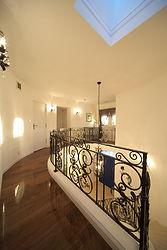 輸入住宅/住宅施工事例/漆喰壁に映えるオリジナルのロートアイアン手摺のある廊下。