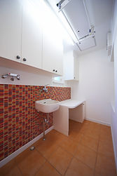 輸入住宅/住宅施工事例/キッチンに続く家事室は赤いガラスが特徴。