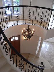 住宅施工例。円形の空間が広がり、アールを描いた階段が続くエントランス。輸入シャンデリア。
