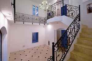 住宅施工事例。2種類の大理石を用いてデザイン張りした床、床の大理石と同じ石で仕上げた階段、アイアンの手摺りはプレジールメゾンの定番。