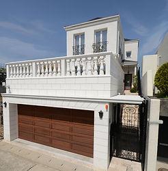 輸入住宅/住宅施工事例/白亜の壁が眩しいガレージ付きの邸宅。外壁と外構には漆喰と白いライムストーンを採用。