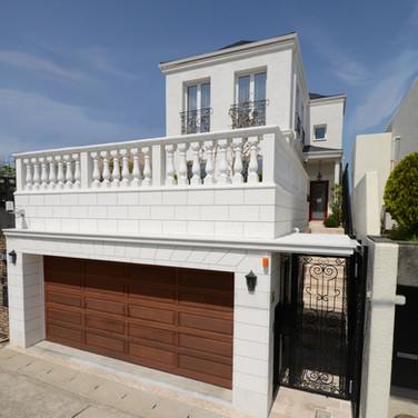 住宅施工例。白亜の壁が眩しいガレージ付きの邸宅。