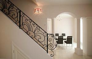 輸入住宅/住宅施工事例/柔らかい色合いの漆喰壁と、階段のアイアン手摺が美しい空間。