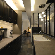 白と黒でシックにまとめたキッチン。ガラス窓の向こうはリビング、見渡すことが出来る。