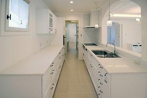 輸入住宅/住宅施工事例/ホワイトで統一したキッチン。キッチンの横にはパントリーを設置し収納スペースを確保。